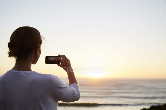Woman photographing sunset over ocean with camera phone — Stock Photo
