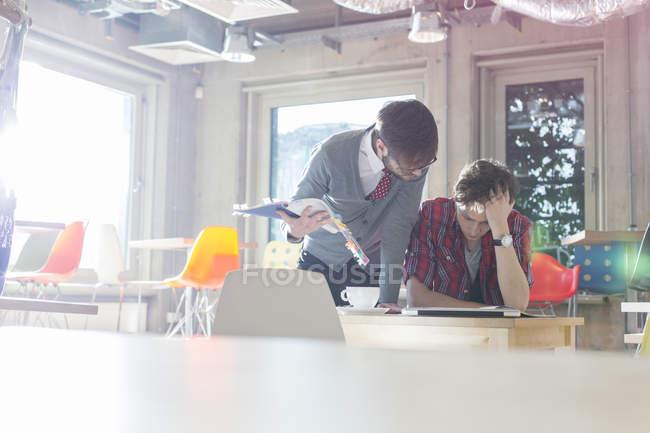 Empresários criativos rever edições de documento em escritório ensolarado — Fotografia de Stock