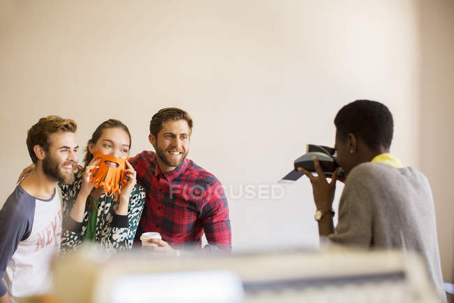 Creative business people playfully posing for coworker with instant camera — Stock Photo