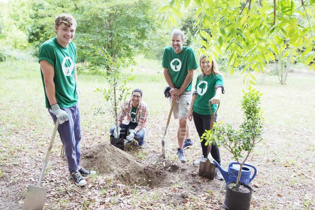 Portrait de bénévoles écologistes confiants plantant un nouvel arbre — Photo de stock