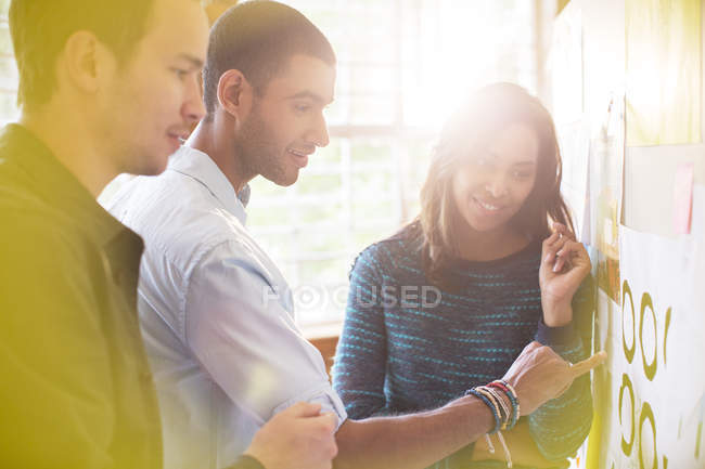 Business people examining proofs on board — Stock Photo