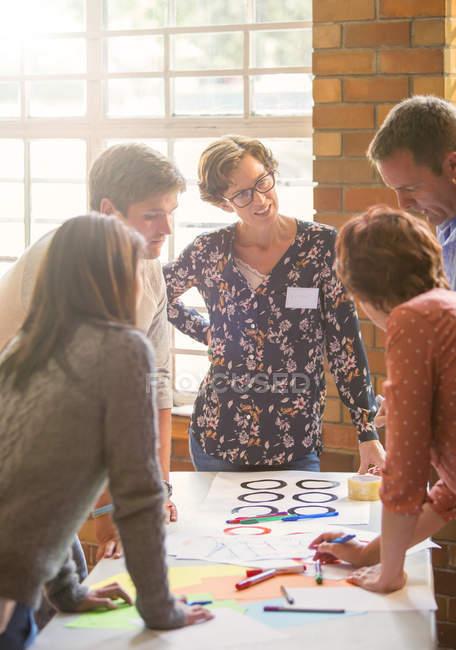 Kreative Geschäftsleute begutachten Beweise am Tisch — Stockfoto