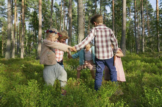 Meninos e meninas de mãos dadas no círculo entre árvores na floresta — Fotografia de Stock