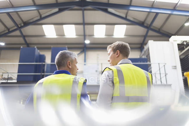 Supervisor and worker talking in steel factory — Stock Photo