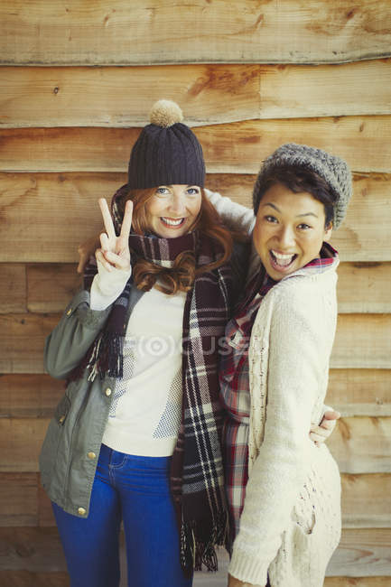Portrait smiling female friends gesturing peace sign outside cabin — Stock Photo
