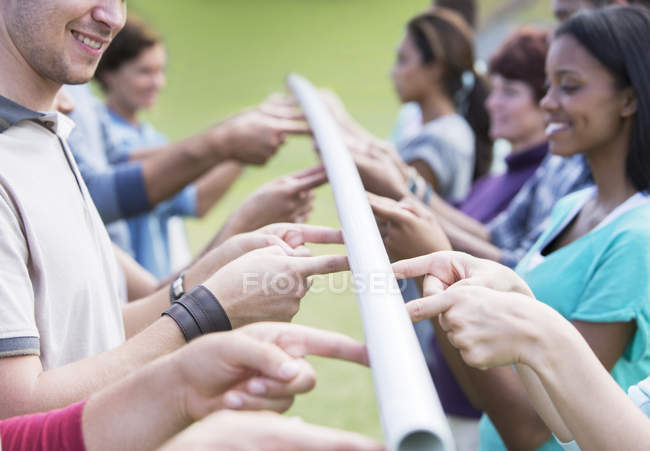 Team balancing pole with fingertips — Stock Photo