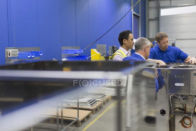 Workers examining equipment in steel factory — Stock Photo