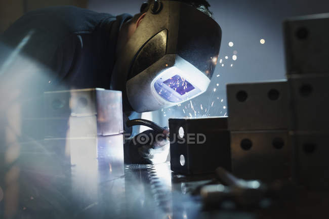 Welder using welding torch on steel in steel factory — Stock Photo