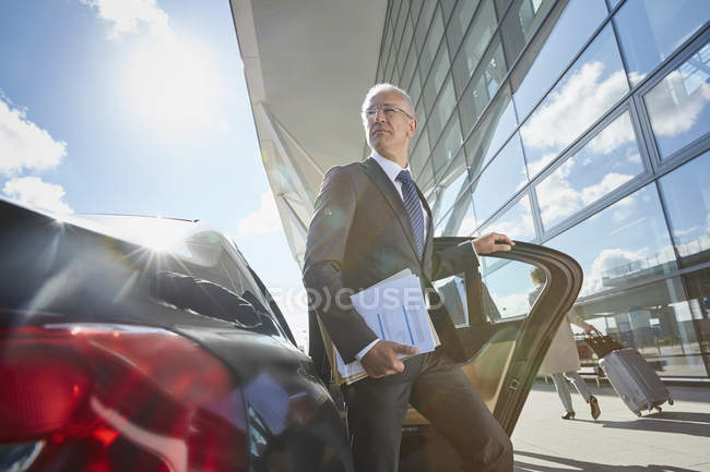 Businessman arriving at airport getting out of town car — Stock Photo