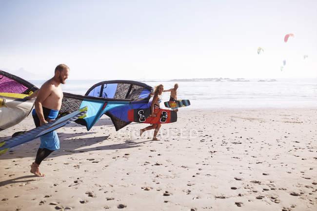 Друзі, які працюють з Кайтбордінг повітряних зміїв на сонячному пляжі — стокове фото