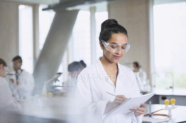 Studente di college femminile prendere appunti in aula laboratorio di scienze — Foto stock