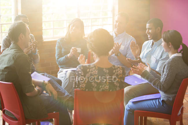Group therapy session clapping in circle — Stock Photo