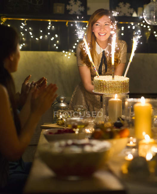 Enthusiastic woman serving cake with sparkler fireworks to clapping friends — Stock Photo