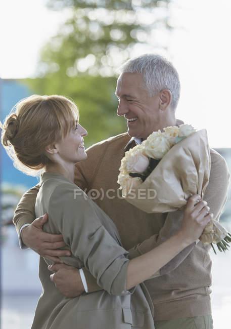 Lächelndes Paar mit Blumenstrauß umarmt — Stockfoto