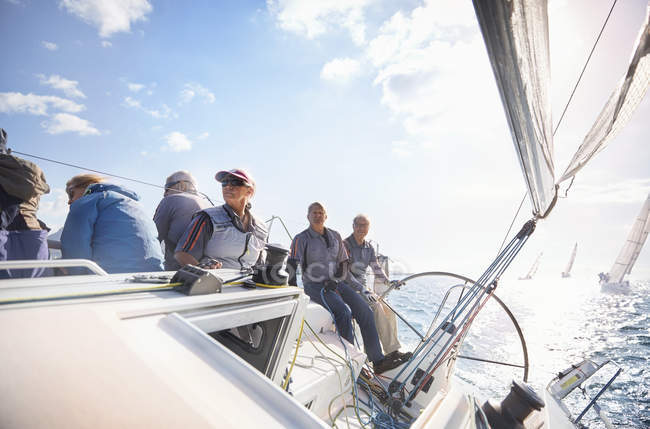 Retired friends on sailboat on sunny ocean — Stock Photo