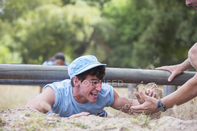 Teammate helping man crawling on boot camp obstacle course — Stock Photo