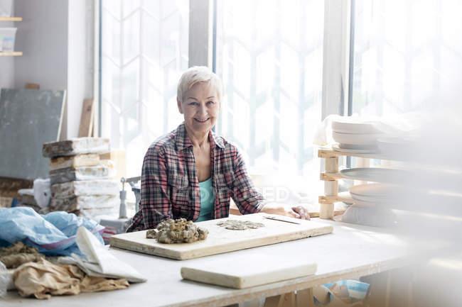 Retrato sonriente mujer trabajo con la arcilla en estudio de la cerámica - foto de stock