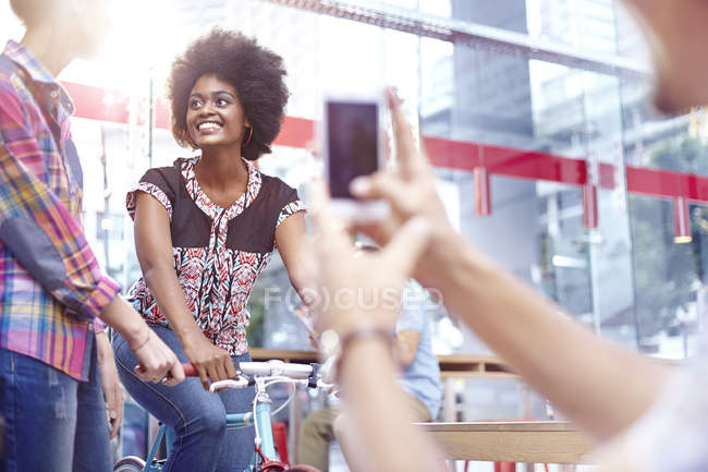 Man photographing women in modern cafe — Stock Photo