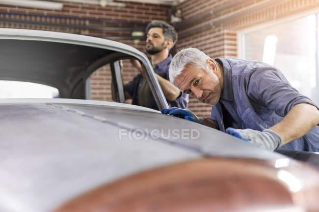 Foco mecânico examinar o painel do carro clássico em oficina de reparação automóvel — Fotografia de Stock