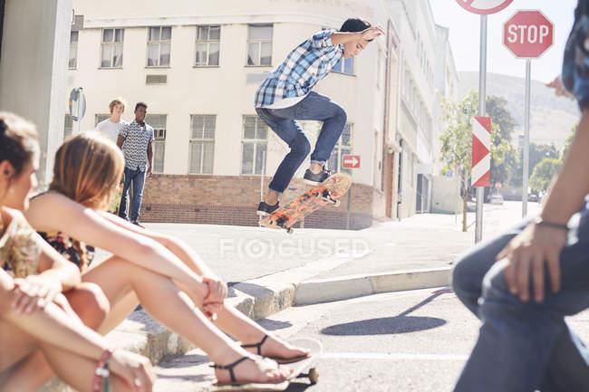 Friends watching teenage boy jumping skateboard at sunny urban corner — Stock Photo