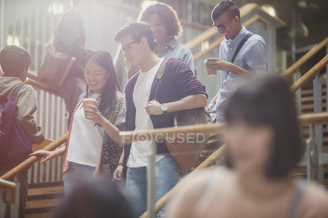 College students talking and descending stairway — Stock Photo