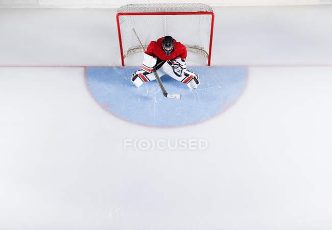 Хоккейный вратарь в красной форме защищает сетку ворот — стоковое фото