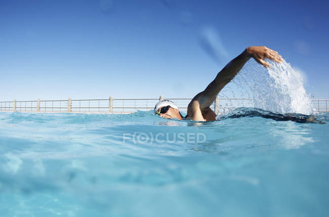 Male swimmer athlete swimming in sunny swimming pool — Stock Photo