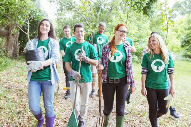 Smiling environmentalist volunteers planting new tree — Stock Photo