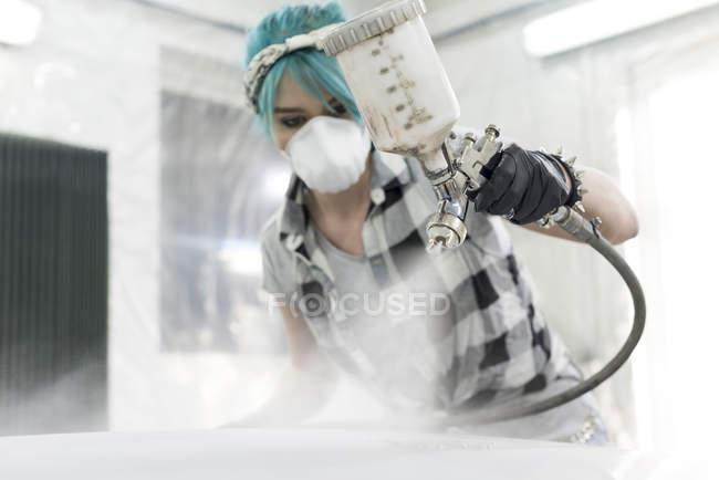 Mujer joven en coche de pintura de aerosol de máscara protectora en la tienda de cuerpo auto - foto de stock