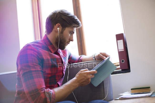 Случайные бизнесмен с наушниками и цифрового планшета — стоковое фото