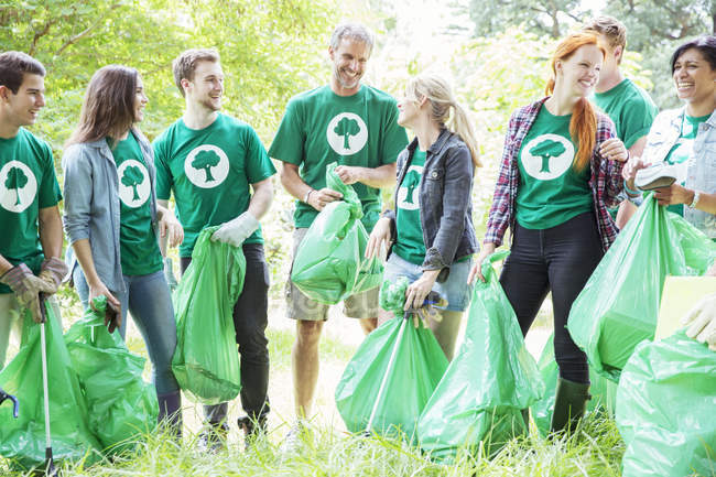 Smiling environmentalist volunteers picking up trash — Stock Photo