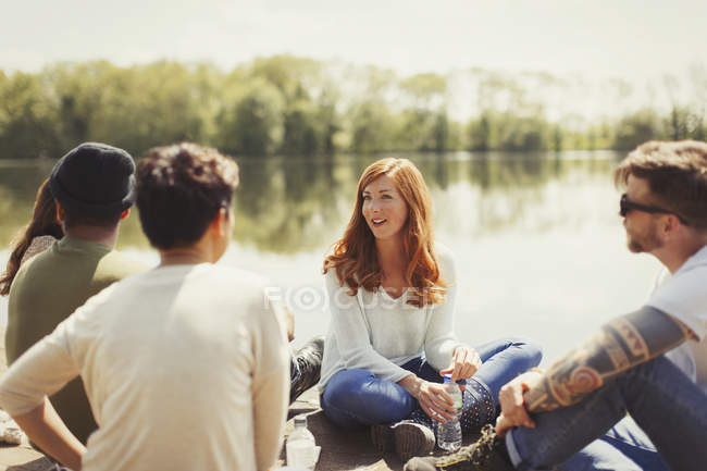 Friends talking at sunny lakeside — Stock Photo