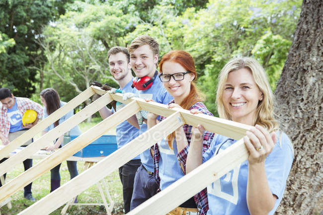 Portrait of smiling volunteers lifting construction frame — Stock Photo