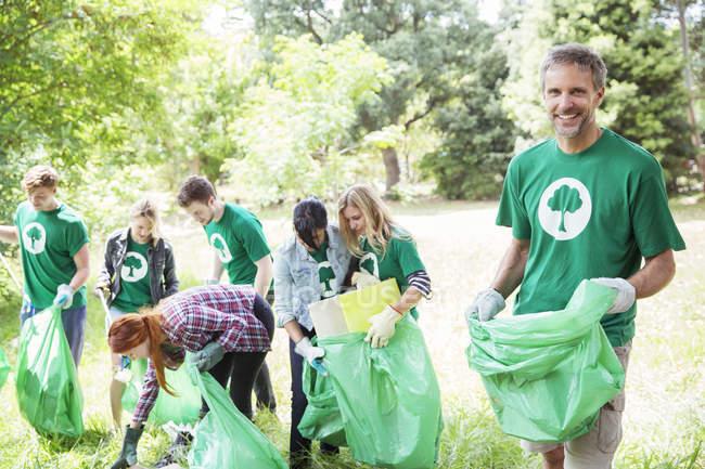 Portrait of smiling environmentalist volunteer picking up trash — Stock Photo