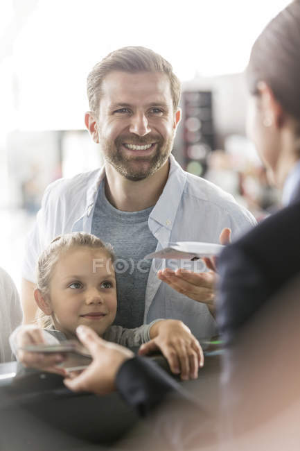 Father and daughter with airplane tickets at airport check-in counter — Stock Photo