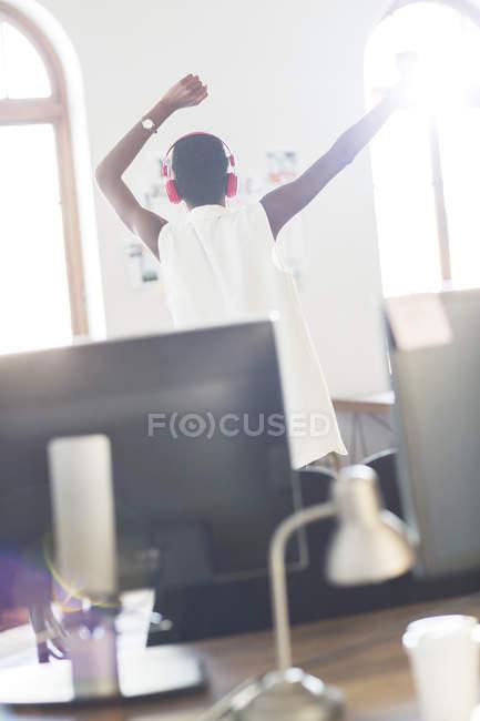 Gelegenheitsunternehmerin mit Kopfhörern tanzt im Büro — Stockfoto