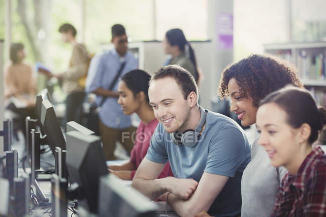 Étudiants utilisant des ordinateurs dans une bibliothèque de laboratoire informatique — Photo de stock