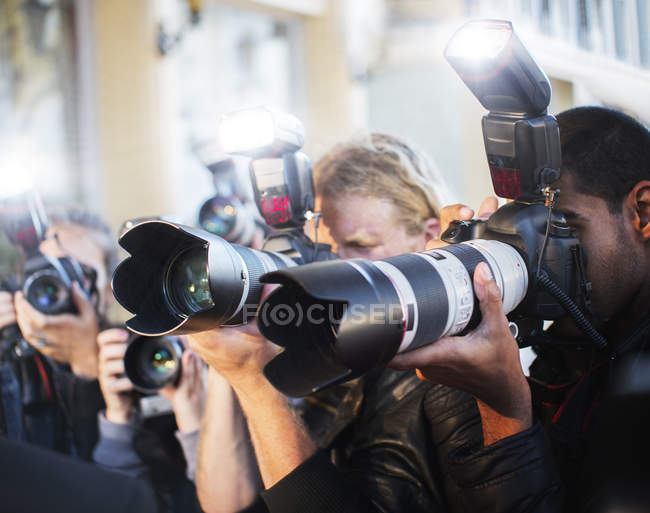 Close up of paparazzi photographers pointing cameras at event — Stock Photo