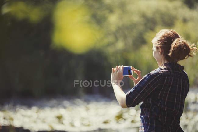 Женщина с телефоном на солнечном берегу озера — стоковое фото