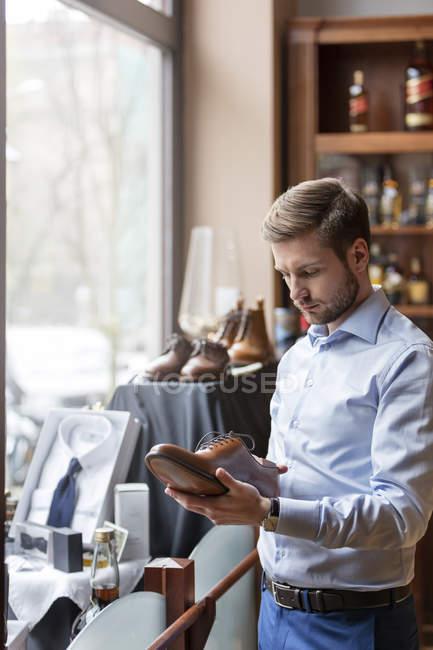 Бизнесмен покупает мужскую обувь в магазине мужской одежды — стоковое фото