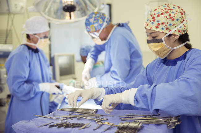 Chirurgien au plateau de ciseaux chirurgicaux en salle d'opération — Photo de stock