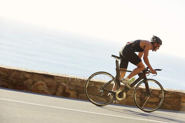 Triathlet rast auf Meeresstraße — Stockfoto