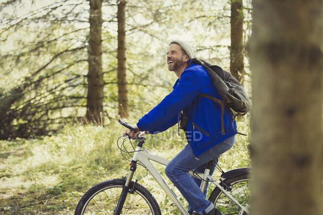 Smiling man riding mountain biking in woods — Stock Photo