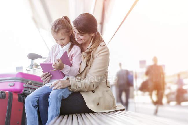 Mère et fille utilisant la tablette numérique sur le banc à l'extérieur de l'aéroport — Photo de stock