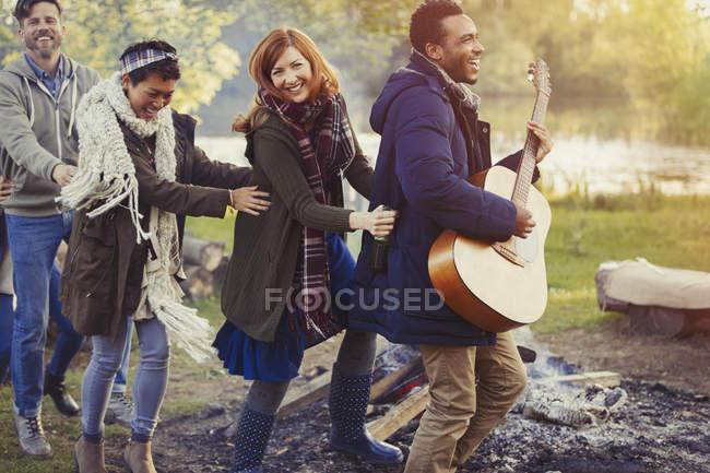 Amici giocosi con la chitarra che ballano in fila in conga al campeggio — Foto stock