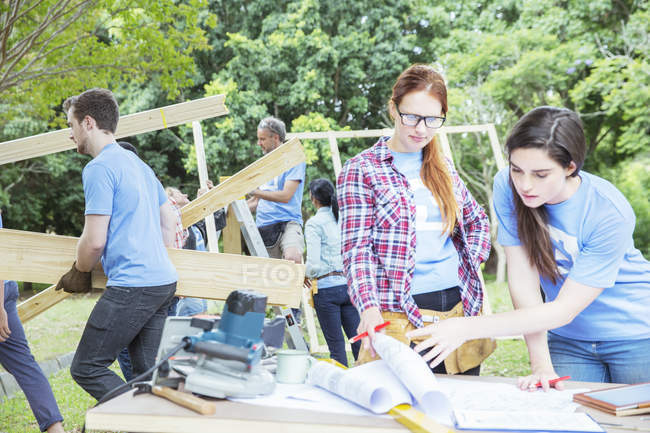 Volunteers reviewing blueprints at construction site — Stock Photo