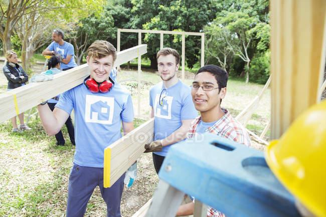 Portrait de bénévoles souriants tenant des planches sur le chantier — Photo de stock