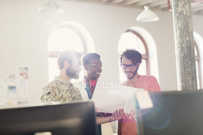 Creative business people reviewing paperwork in sunny office — Stock Photo
