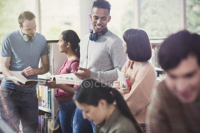 Estudiantes de la Universidad hablando y estudiando en la biblioteca - foto de stock