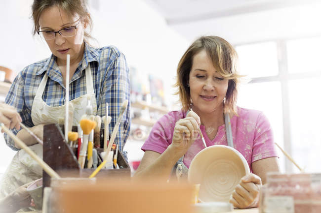 Mature women painting pottery in studio — Stock Photo